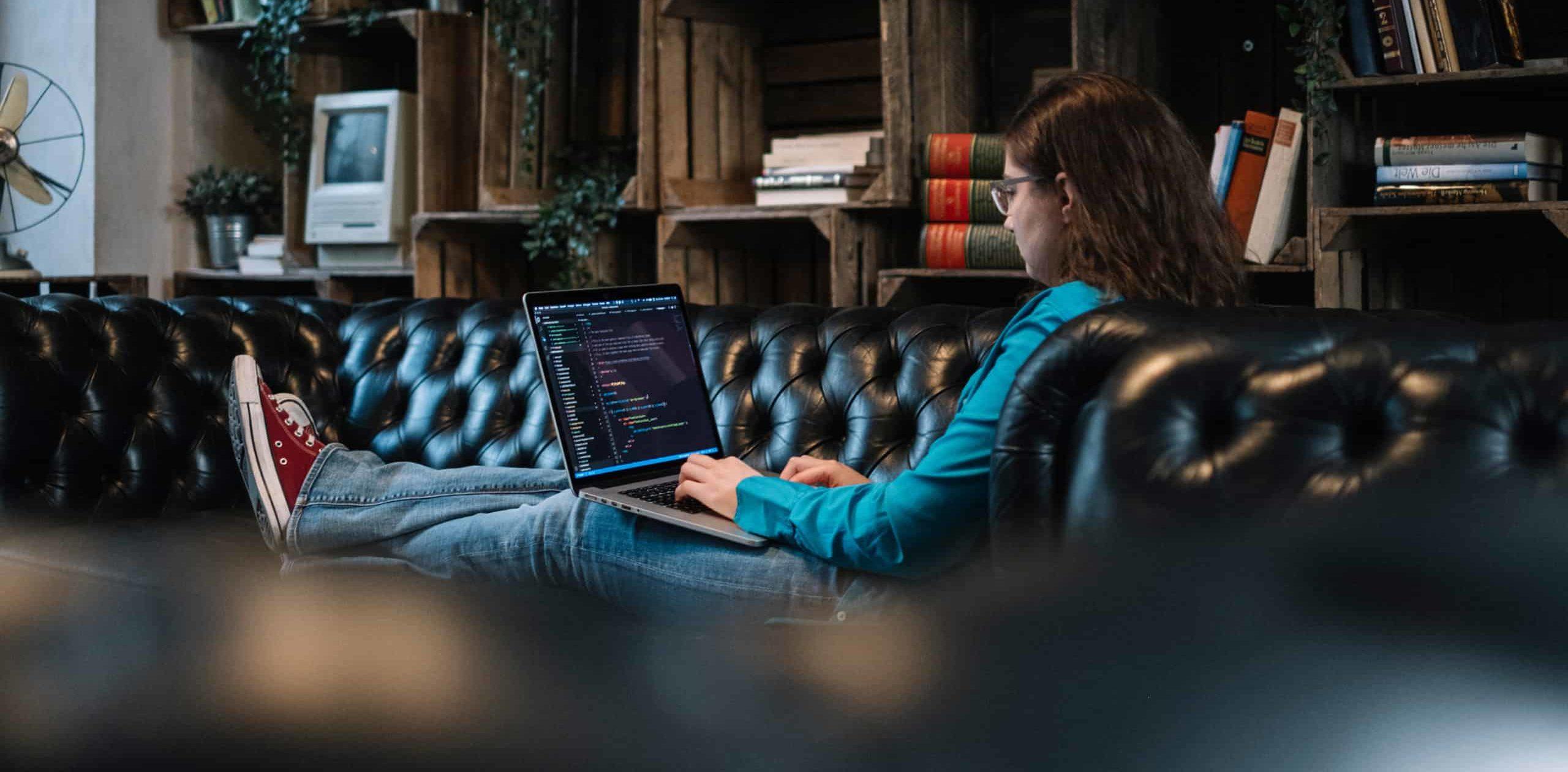 Jessica sitzt auf einem schwarzen Sofa und programmiert auf ihrem MacBook.