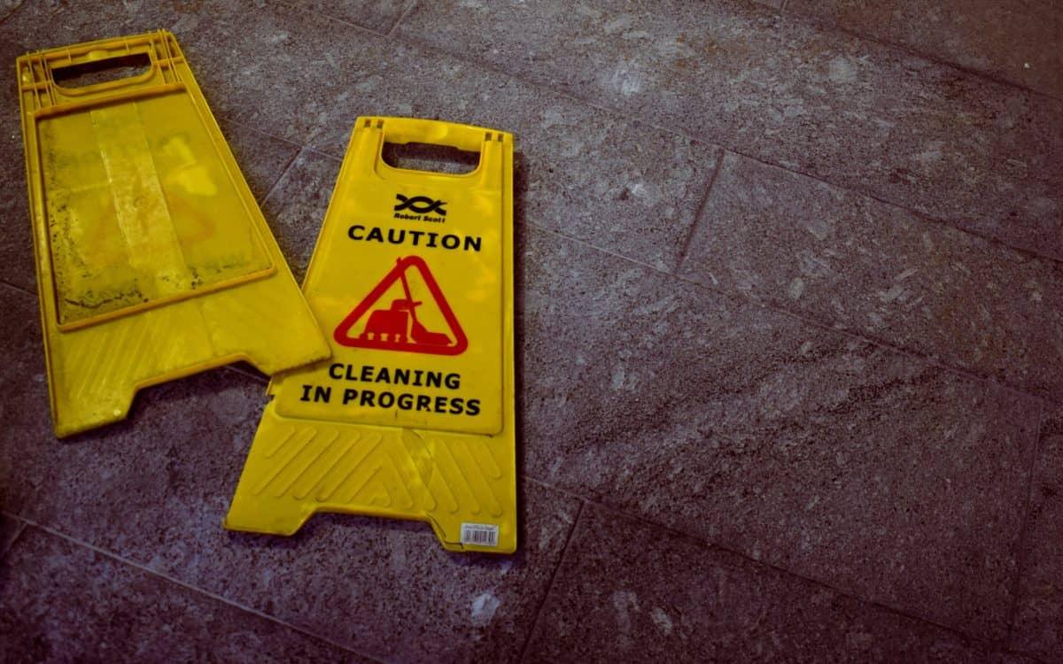 """Zwei Aufsteller mit der Aufschrift """"Caution - Cleaning in Progress"""" liegen auf einem Steinboden"""