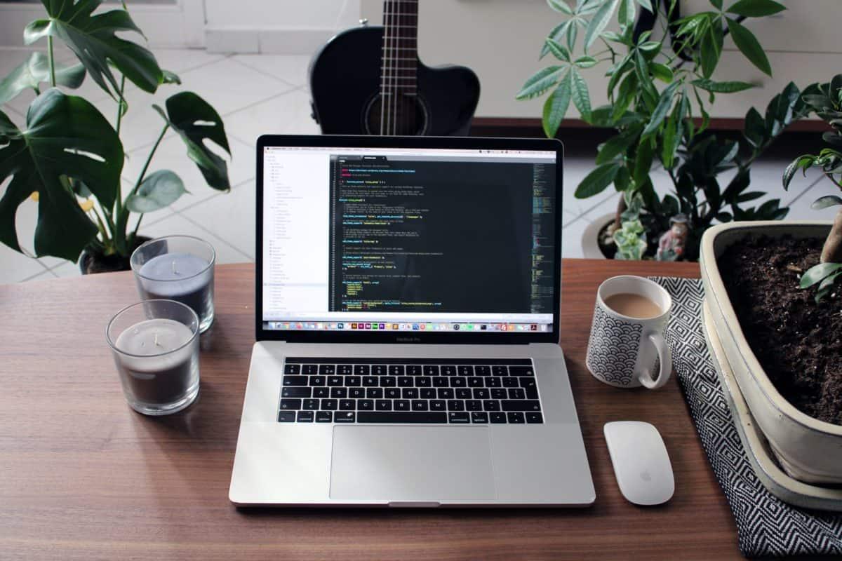 Macbook auf einem Schreibtisch, umgeben von Dekoelementen